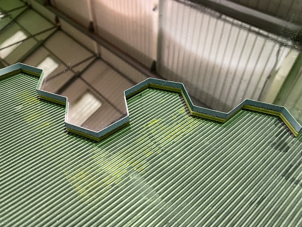hexagonal pattern waterjet cut into a 6mm glass mirror close up